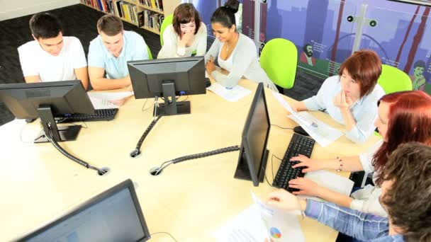 Group of diverse students using information library
