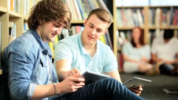 giovani studenti maschi networking su tavolette in università