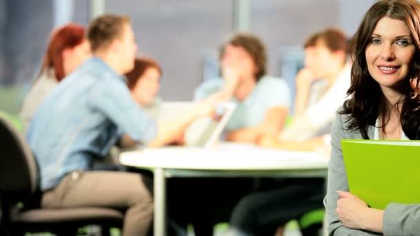 Portrait of brunette tutor learning students in classroom