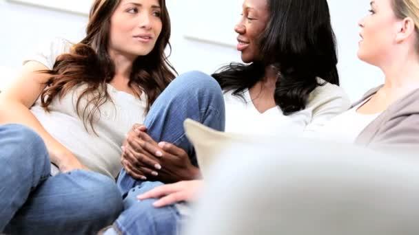 multi etnico ragazze spettegolare sul divano in casa moderna