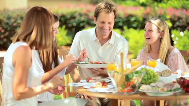 Family sharing healthy lunch in garden