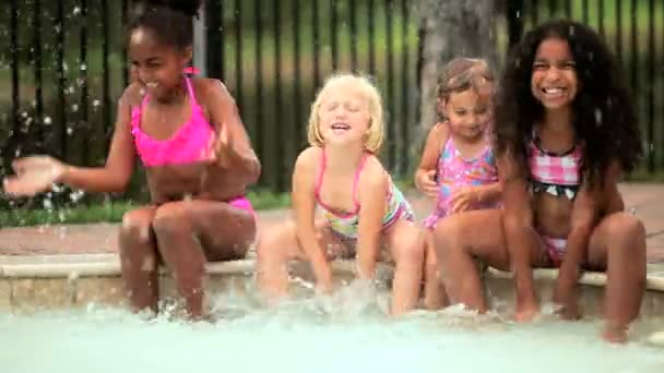 Multi etnikai lányok fröcskölik egymást-medencében