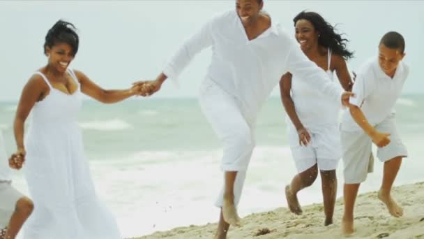 Happy ethnic family running and laughing together by ocean