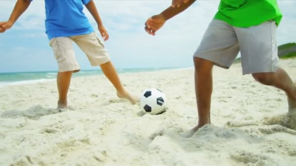 Diverse brothers kicking together football on beach