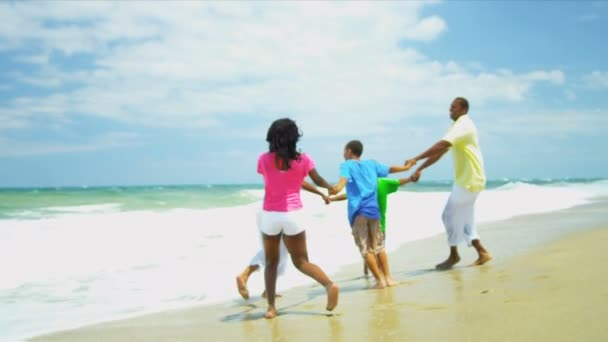 Ethnic family walking on holiday together on beach holding hands