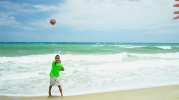 mladí etnické přátelé chytat míč americký fotbal na pláži