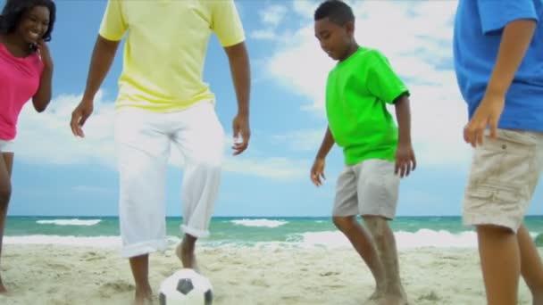 African American family spending summer kicking soccer ball on beach