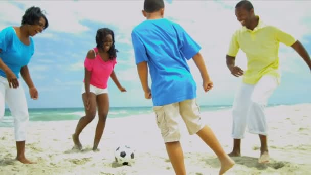 Football game of ethnic parents wit young sons and teenage daughter on beach