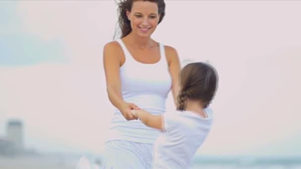 Kavkazská dívka líbí čas společně matka oblečená v bílém na pláži