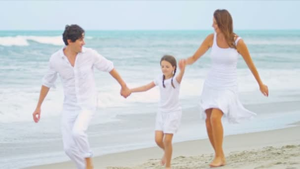Caucasian parents walking holding hands together young daughter by ocean