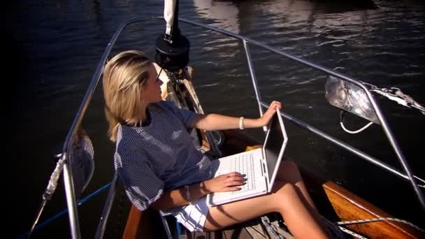 Beautiful blonde girl with her laptop aboard a luxury yacht