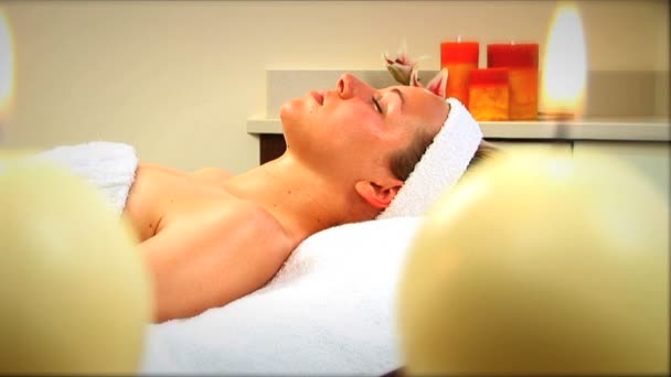 Beautiful blonde girl relaxing at health spa with candles burning