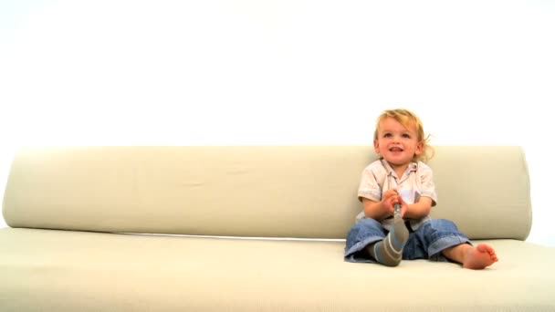 Cute caucasian toddler playing on a sofa and taking his socks off
