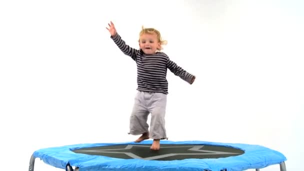 Cute little blonde boy playing on a trampoline