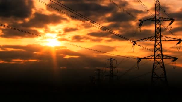 Time-lapse clouds at sunset over electricity pylons