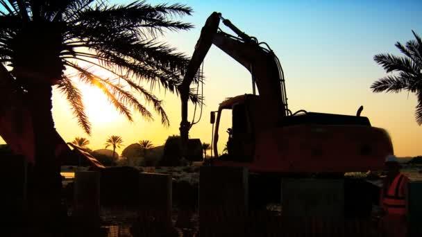 meccanico escavatore in sagoma, lavorando sul cantiere al tramonto