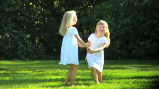 Young child sisters having fun together outdoors on a summers day