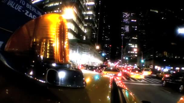Point-of-view of yellow taxi cabs driving the streets at night in New York City, USA