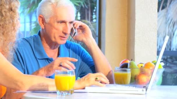Atraktivní starší pár pomocí notebooku  mobil k zajištění budoucí plány
