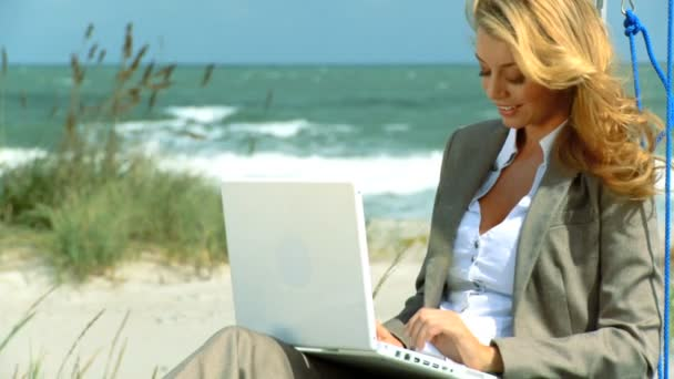 Beautiful blonde businesswoman using technology to work from the beach