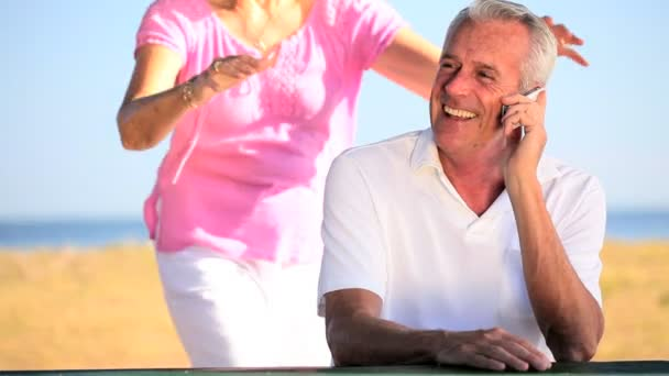 Retired Couple Using Cell Phone