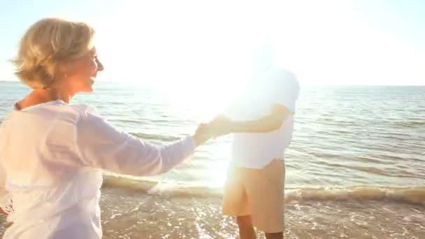 romantický senioři tančí na pláži