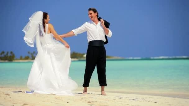 Coppie di cerimonia nuziale che ride  ballando sulla spiaggia