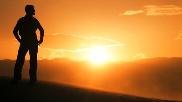 Magányos nő a sziluett, túrázás keresztül homokdűnék  nézni a lenyugvó nap