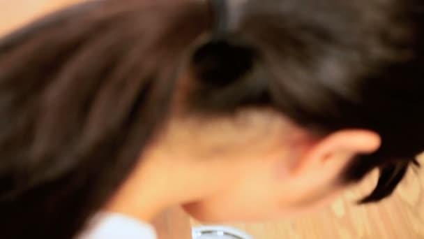 Asijská dívka sama váží na vahách