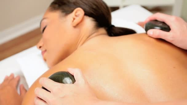 Female Spa Client Receiving Hot Stone Massage