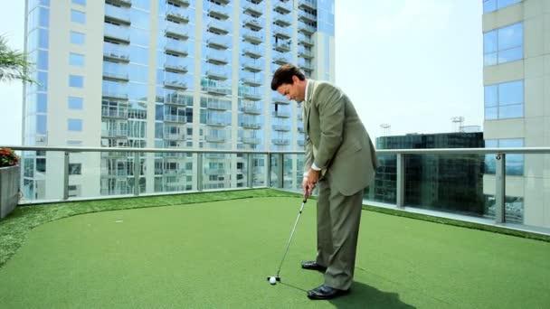 mladý podnikatel cvičit golf na střeše úřadu města