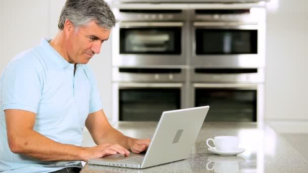 středního věku muž s notebookem na kuchyňské lince