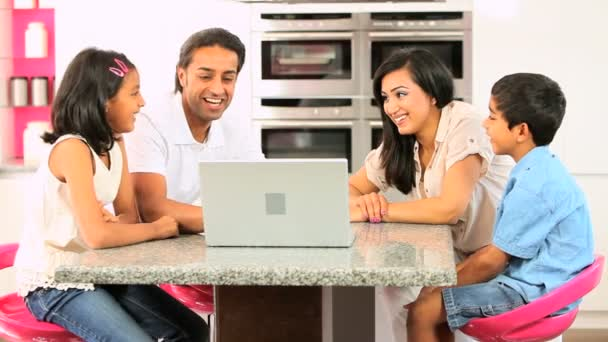 mladá asijská rodina s notebookem v kuchyni