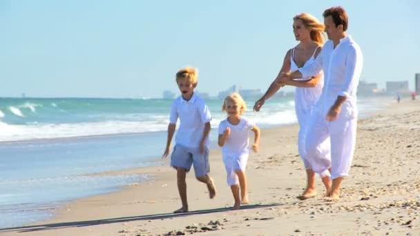 Happy Caucasian Family Splashing in Ocean Shallows