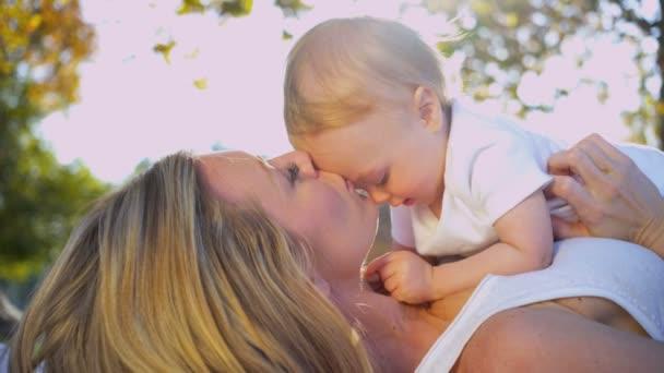 mladá maminka venku něžně líbat její dítě
