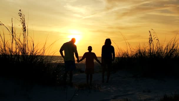 Parents and son watching sunset