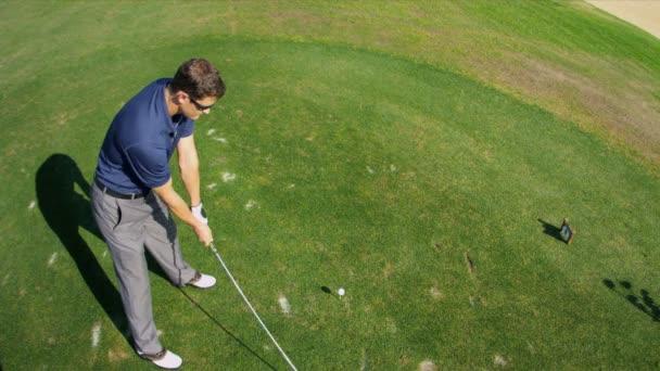 Professional golfer hitting golf ball