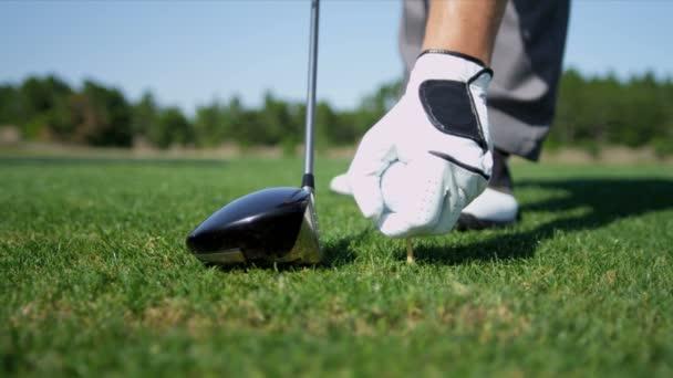 Golfer platzieren Golfball auf tee