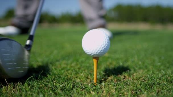 golfista udeří míč z odpaliště