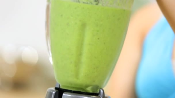 Healthy young Caucasian girl at  home kitchen blending tasty nutritious fresh vegetable smoothie