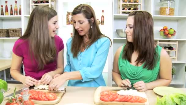Teenage girls at  home kitchen helping their mom