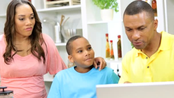 Family cooks in the kitchen with laptop