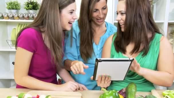 Kavkazská maminka a dospívajících dívek pomocí technologie bezdrátové tablet v domácí kuchyni