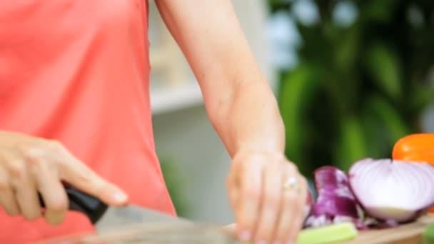 θηλυκό τεμαχισμός των λαχανικών στην κουζίνα