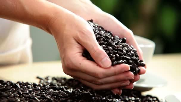 Hände nur frische Kaffeebohnen von Frauenhänden Gießen