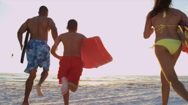 Family running to ocean