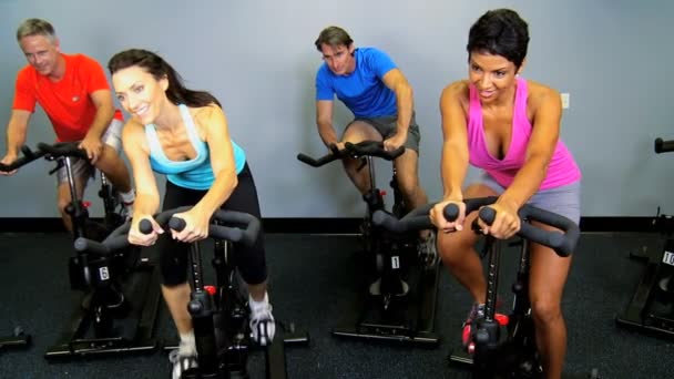 Gym members on exercise bikes