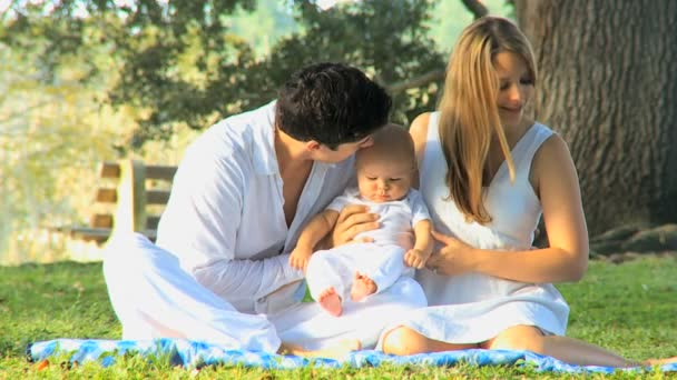 Young couple playing with baby in the park
