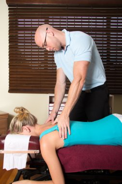 Chiropractor treating patient back with pressure