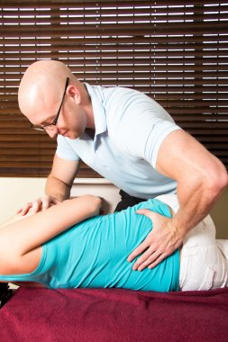 Chiropractor press female patient lower back